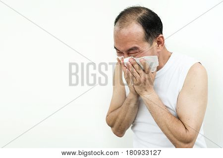 Asian senior man sneezing with tissue. Illness allergy diseases cold flu concept. Copy space.