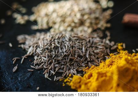 Cumin Seeds Surrounded By Spices Over Black Surface.