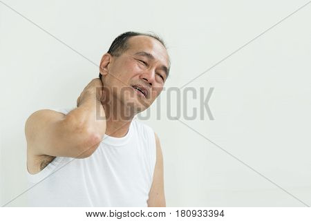Asian senior man having pain on his shoulder and neck. copy space.