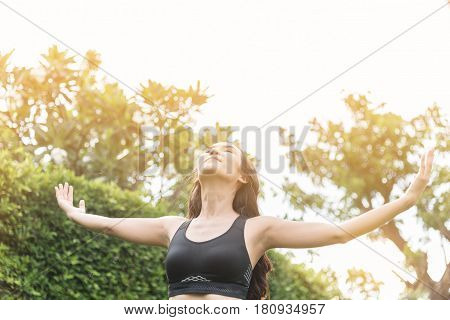 Happiness of Asian woman in sportswear relaxing with beautiful nature and breathing fresh air.