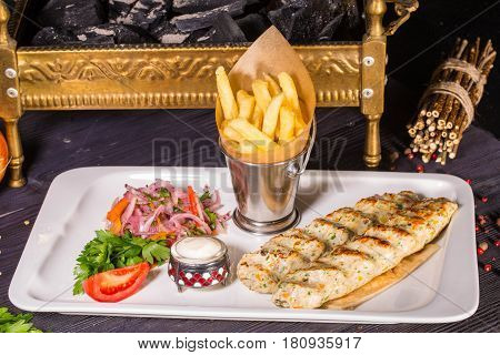 Kebab from chicken forcemeat, is served with creamy sauce, French fries and onions salad