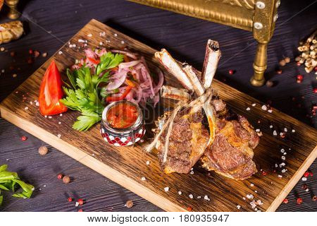 Pieces of mutton tenderloin on a stone, is served with onions, red pepper, parsley and spices salad, French fries and the Ajika sauce