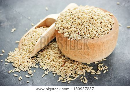 Unpolished rice in wooden bowl on table