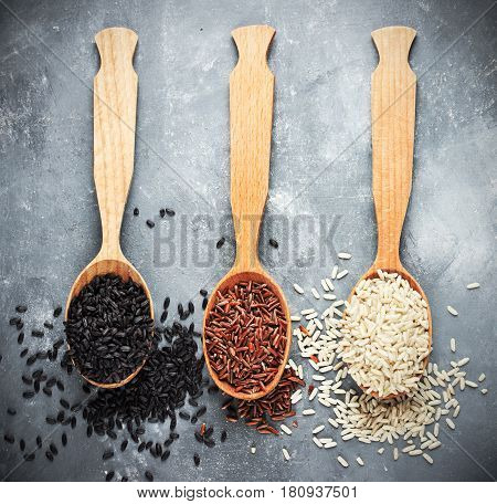 Black rice brown rice red rice in wooden spoons top view