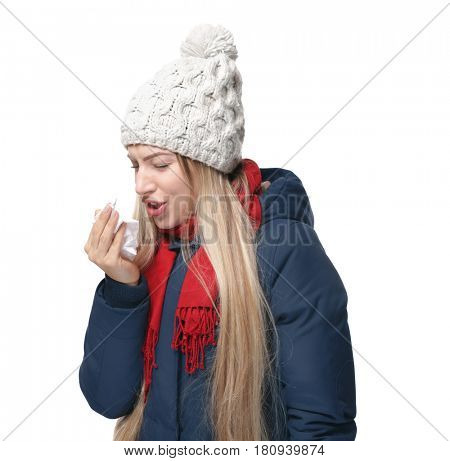 Young woman sneezing in tissue on white background