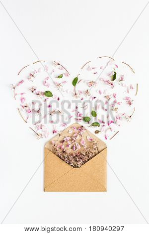 close up of spring flowers poured from envelope in shape of heart on white background. top view. concept of love and proposal. Flat lay. happy valentines day. womens day. 8 of march. mothers day.
