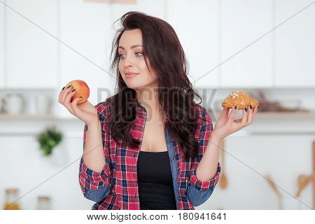 Diet. Dieting concept. Healthy Food. Beautiful Young Woman choosing between Fruits and Sweets. Weight Loss.