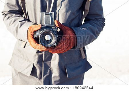 Man hold in hand a vintage old camera on the seashore background