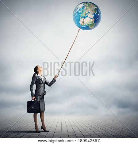 Businessman controlling Earth planet with lead. Elements of this image are furnished by NASA
