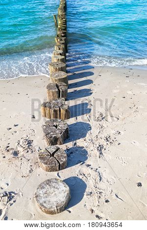 Row of wooden breakwater pillars at beach near Zingst (Darss peninsula, Germany) seen from sand into water and shadow images of it