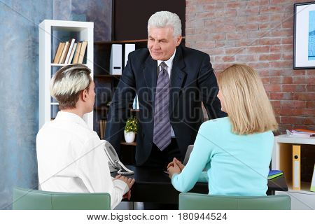 Young woman and son meeting with teacher at school