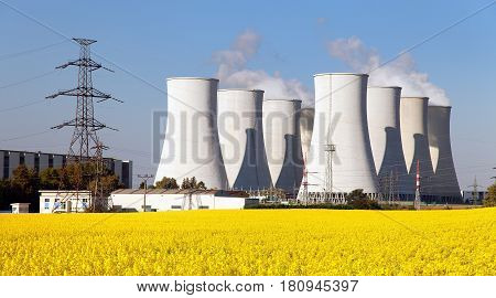 Panoramic view of Nuclear power plant Jaslovske cooling tower Bohunice with golden flowering field of rapeseed - Slovakia - two possibility for production of electric energy
