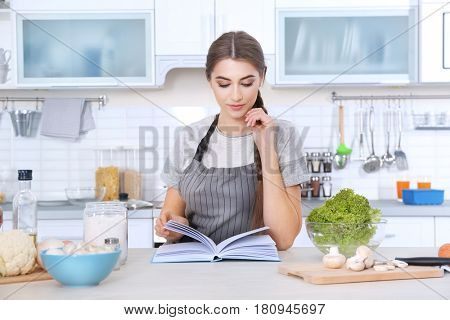 Young woman with cookbook at kitchen table
