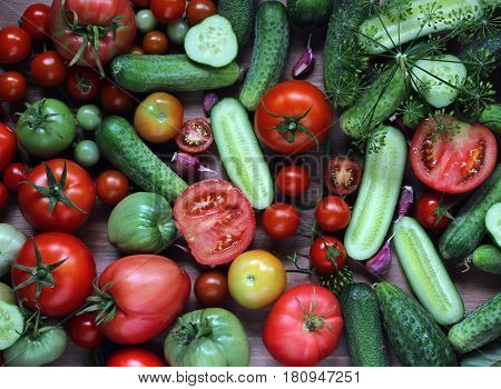 ripe red tomatoes and green cucumbers on the table top view. vegetables food. dark and Moody.