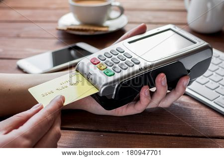 Credit card payment by terminal for business lunch in cafe on wooden table background
