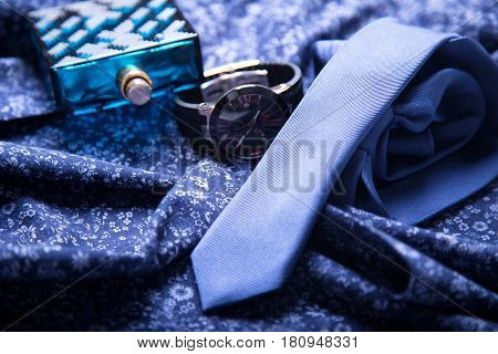 Men's tie, perfume, watch on a blue background