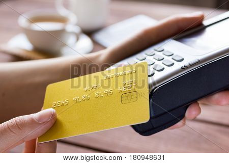 Payment by credit card in cafe with terminal and keyboard and coffee on wooden desk background