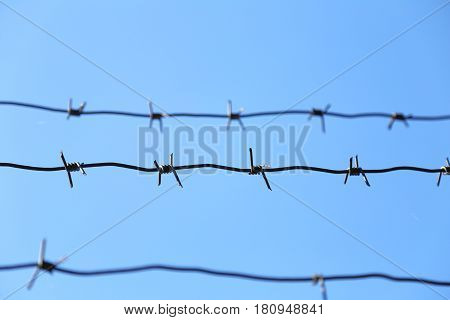 Barbed wire on blue sky background. Barb