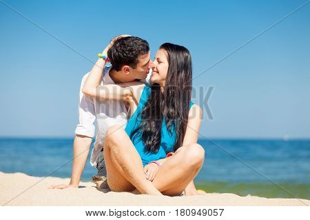 Photo Of Cute Couple Sitting On The Beach And Kissing On The Wonderful Sea Background