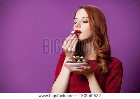 photo of beautiful young woman with plate full of chocolate candies on the wonderful purple background