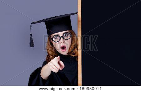 Photo Of Beautiful Young Alumnus With Blackboard On The Wonderful Grey Studio Background