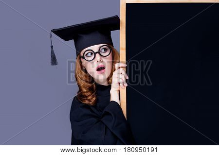 Photo Of Beautiful Young Alumnus With Blackboard On The Wonderful Grey Studio Background