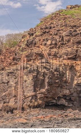 Cliff Ladders: a series of wooden ladders trailing down a cliff side, utilized by fisherman, on Kauai, Hawaii
