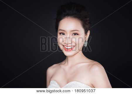Fashion Portrait Of Beautiful Young Asian Woman In White Dress Over Dark Background.