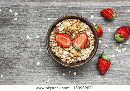 healthy breakfast strawberry muesli with oats granola and nuts in a bowl on rustic wooden table. top view with copy space