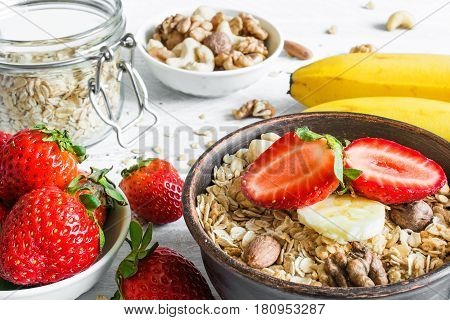 bowl of oat muesli with strawberry banana granola and nuts with ingredients for healthy breakfast on white wooden table. close up