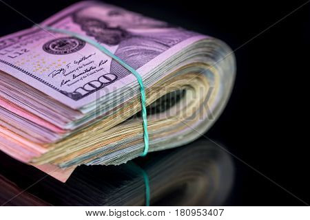 one hundred American dollar banknotes with band isolated on black background.