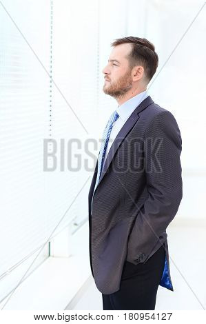 Handsome businessman looking out of the window through the blinds
