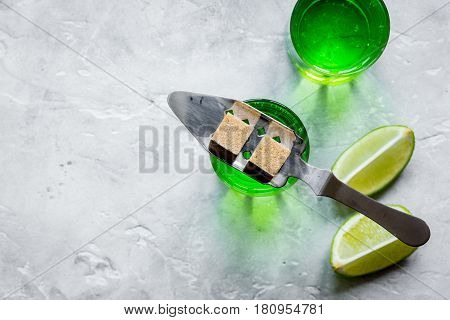 green shots with sugar cubes and fresh lime slices on stone bar table background top view