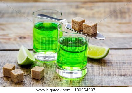 green absinthe in glass with fresh lime slices on wooden table background