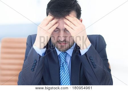 Feeling exhausted. Frustrated young beard man massaging his nose and keeping eyes closed while sitting at his working place