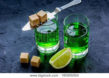 green absinthe in glass with fresh lime slices on dark table background