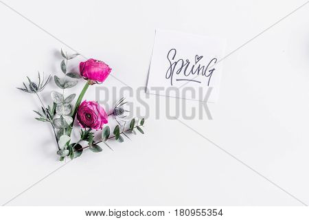 floral concept with pink ranunculus flowers and spring card on white desk background top view mock-up