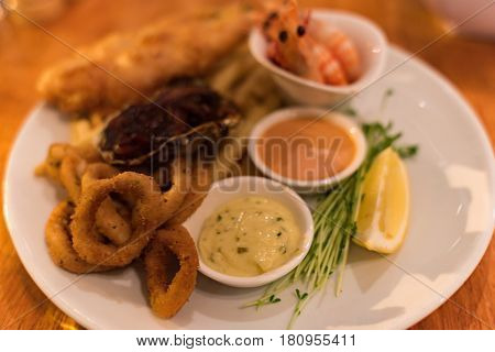 Food Background Of Seafood With Sauce And Fresh Herbs