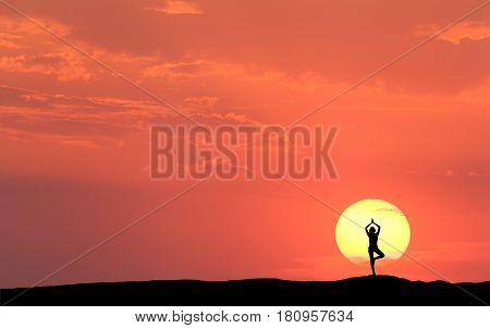 Silhouette of a standing sporty woman practicing yoga with raised up arms on the hill on the background of sun and colorful orange sky with clouds. Landscape with meditating girl at sunset. Fitness