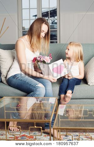 Mother's Day Concept. A Child Girl Congratulates her Mother and Gives Mom a Postcard and Flowers. Mothers and Daughter at Home