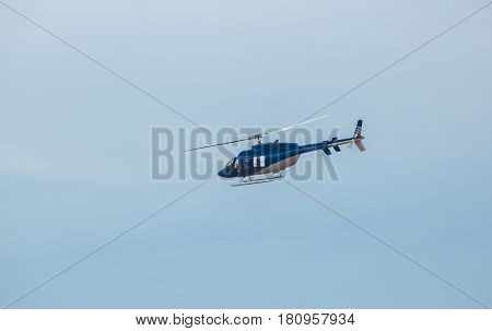 A large blue helicopter is flying against the blue sky.