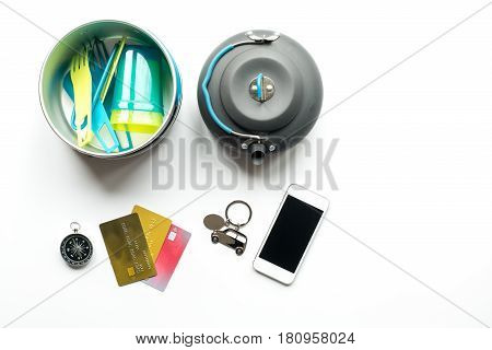 traveller lifestyle items with compass and plactic dishes on white table background top view