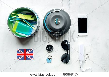 Outfit of traveller with sunglasses and mobile on white table background top view