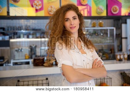 Beautiful female red haired barista looking at camera and smiling while standing with folded arms near the bar counter in cafe