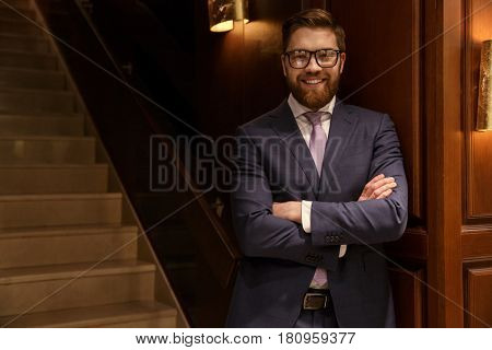 Picture of happy young bearded businessman standing indoors with arms crossed. Looking at camera.