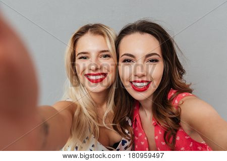 Image of two pretty happy young women posing over grey background. Looking at camera and make selfie.