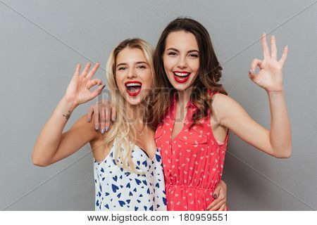 Image of two pretty cheerful young women posing over grey background. Looking at camera and make okay gesture.