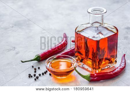 natural oils concept with fresh chili paper and glass jar on stone table background mock up