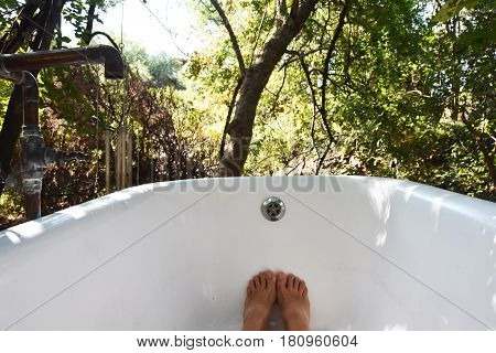 Picture of a person feet only  taking a bath outdoors.