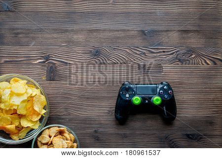 snacks for playing video games with joypad on wooden desk background top view mock-up
